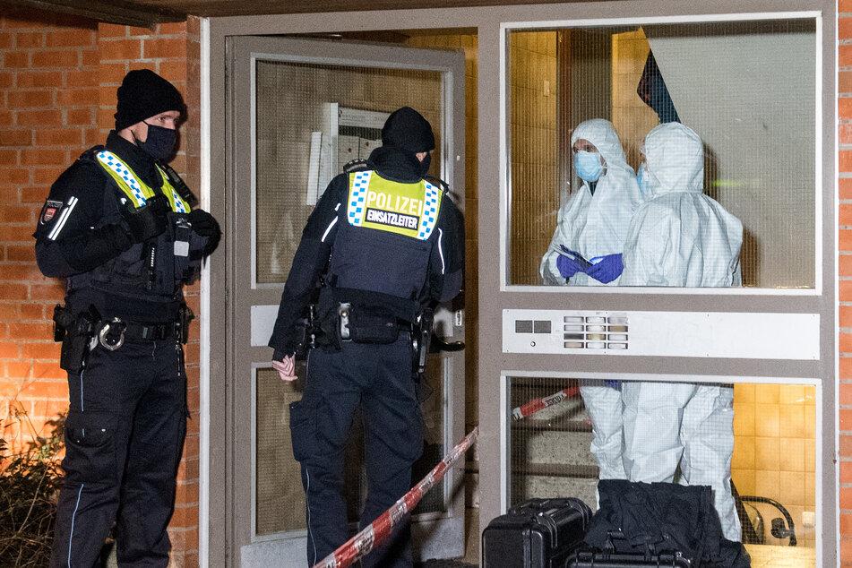 Polizisten und Mitarbeiter der Spurensicherung stehen im Stadtteil Neuallermöhe im Eingang eines Mehrfamilienhauses.