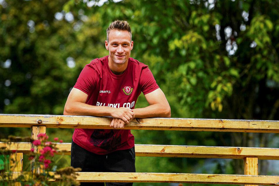 Tim Knipping lächelt in einem Park hinterm Mannschaftshotel der Dynamos in die Kamera des TAG24-Fotografen.