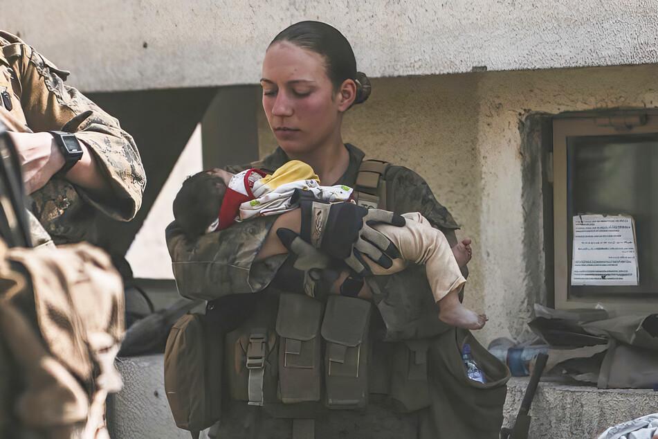 Marineinfanteristin Nicole Gee (†23) steht am Flughafen Kabul und hält schützend ein afghanisches Baby im Arm.