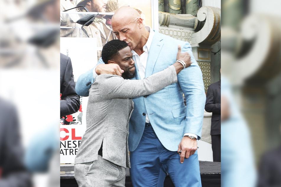 Kevin Hart (l.) hat im Dezember 2019 ein bleibendes Hollywood-Denkmal erhalten. Dwayne Johnson küsst Hart während der Hand- und Fußabdruckzeremonie.