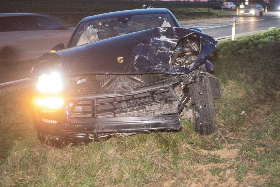 Der Porsche steht nach einem Unfall mit einem Peugeot in einem Grünstreifen. Der Peugeot-Fahrer und sein Beifahrer wurden schwer verletzt.