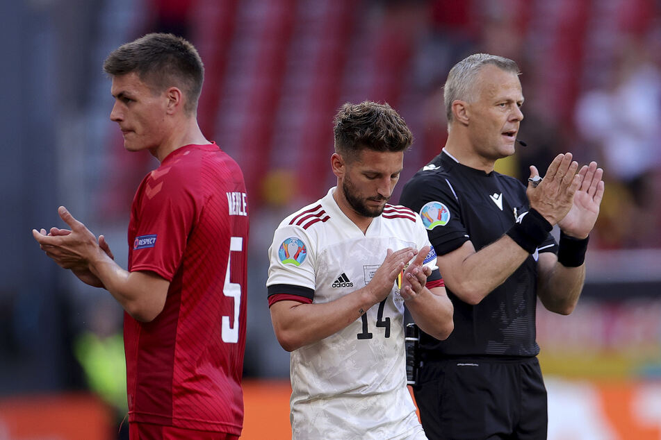 In der 10. Minute wurde die Partie zu Ehren Christian Eriksens unterbrochen. Dänemarks Joakim Maehle (l.), Belgiens Dries Mertens (M.) und Schiedsrichter Björn Kuipers applaudierten zusammen mit den Fans.