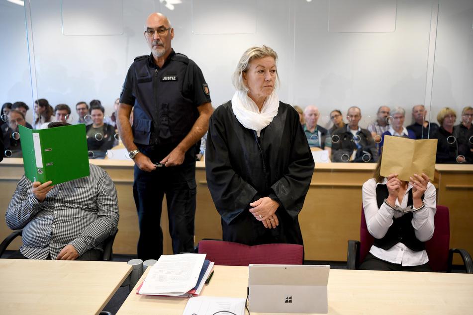 Mit verdeckten Gesichtern sitzt das angeklagte Liebespaar zum Auftakt des Mordprozesses im Gerichtssaal.