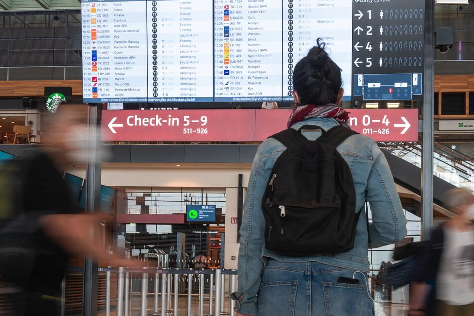 Berlin: Eine Frau steht vor einer Anzeigetafel im Terminal des Flughafens Berlin-Brandenburg (BER). Die Ausbreitung der Delta-Variante in Europa trübt die Urlaubsaussichten.