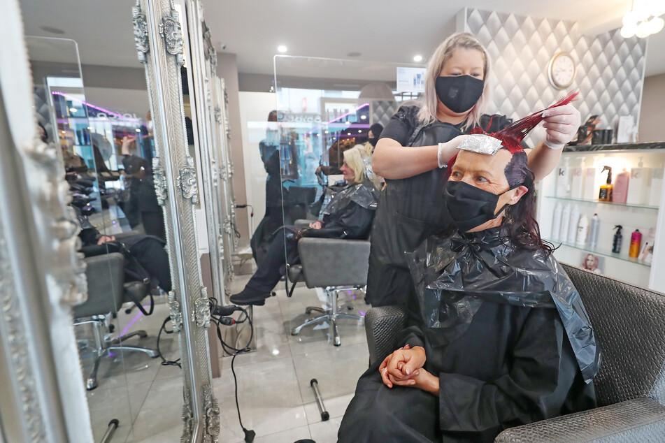 Eine Frau lässt sich mit Mundschutz bei einem Friseur die Haare färben. (Archivbild)