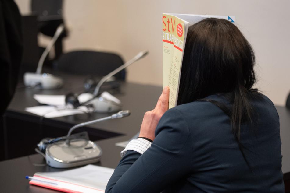 Omaima A. verbirgt ihr Gesicht vor Prozessbeginn hinter einem Heft.