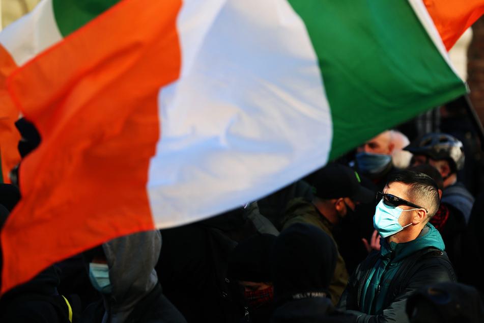 Ein Gegendemonstrant steht während eines Protests gegen Corona-Maßnahmen vor dem Leinster House, dem Sitz des Parlaments.