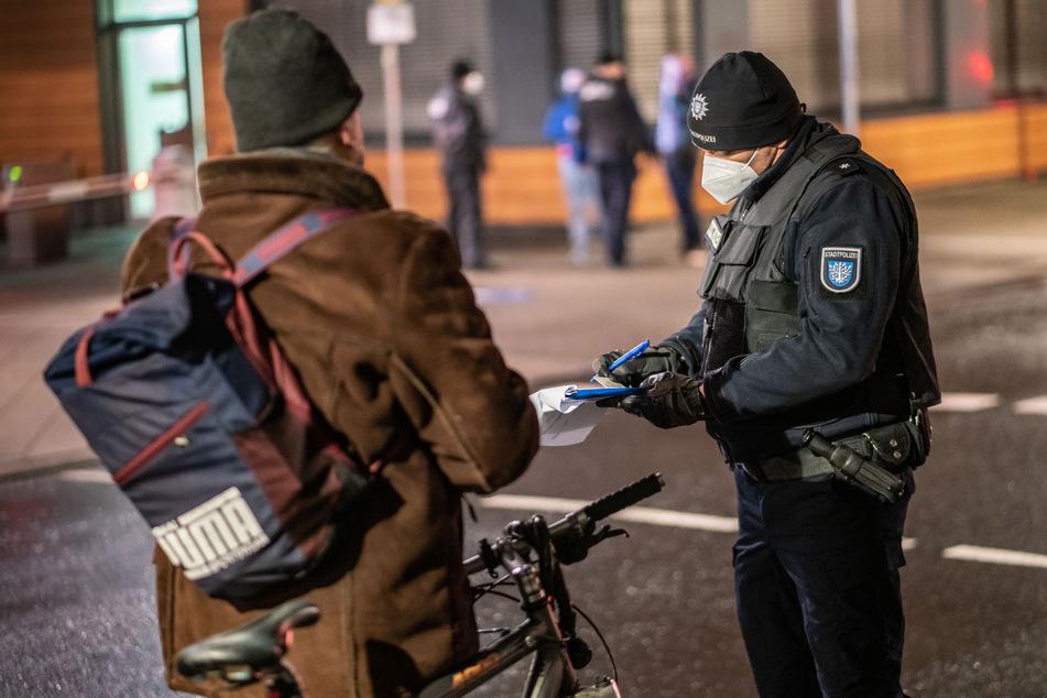 Ein Polizist nimmt die Personalien eines Radfahrers auf, der trotz einer nächtlichen Ausgangsbeschränkung unterwegs ist. (Symbolfoto)