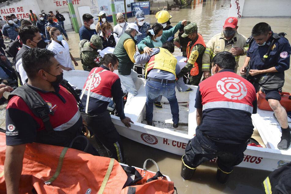 Rettungskräfte tragen eine Frau, nachdem sie sie aus dem Allgemeinen Krankenhaus evakuiert haben.