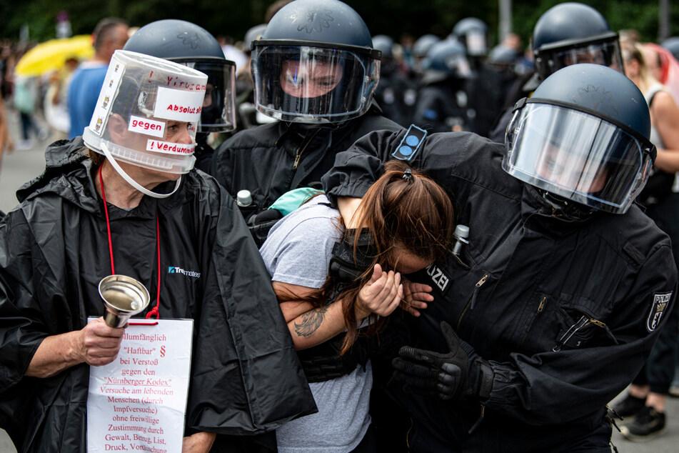 Polizisten nehmen eine Demonstrantin bei einer unangemeldeten Demonstration an der Siegessäule fest. Immer wieder kam es zu Auseinandersetzungen mit der Polizei, auch ein Journalist hat die Aggressivität zu spüren bekommen.