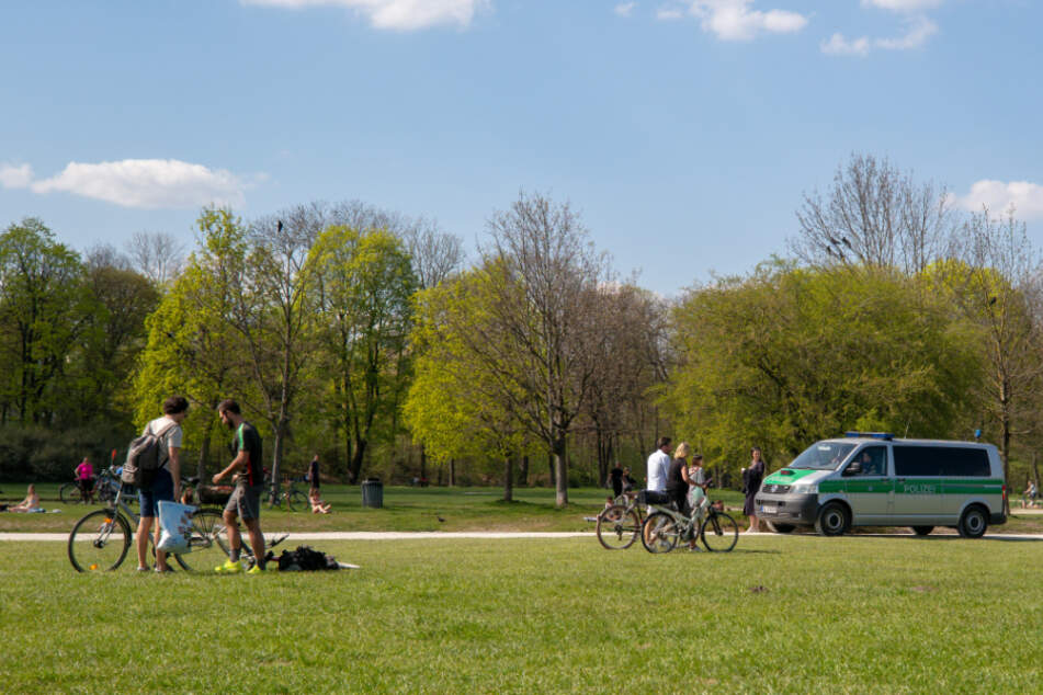 Polizisten fahren in einem Einsatzwagen durch den Englischen Garten im Herzen der Stadt.