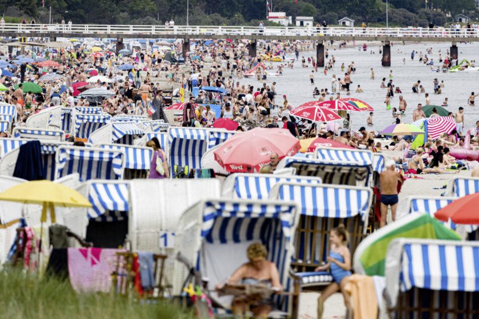 Schleswig-Holstein, Timmendorfer Strand: Badegäste geniessen bei schwülen 26 Grad Lufttemperatur und diesigem Himmel den Nachmittag am Ostseestrand.