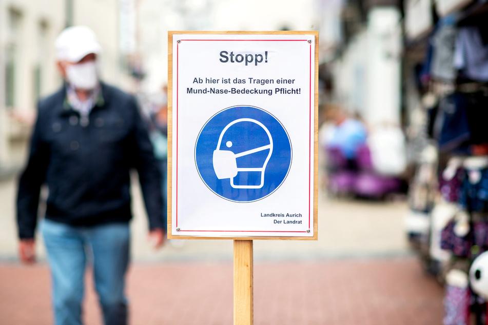 """Ein Schild mit der Aufschrift """"Stopp! Ab hier ist das Tragen einer Mund-Nasen-Bedeckung Pflicht!"""" steht in der Fußgängerzone der niedersächsischen Insel Norderney."""