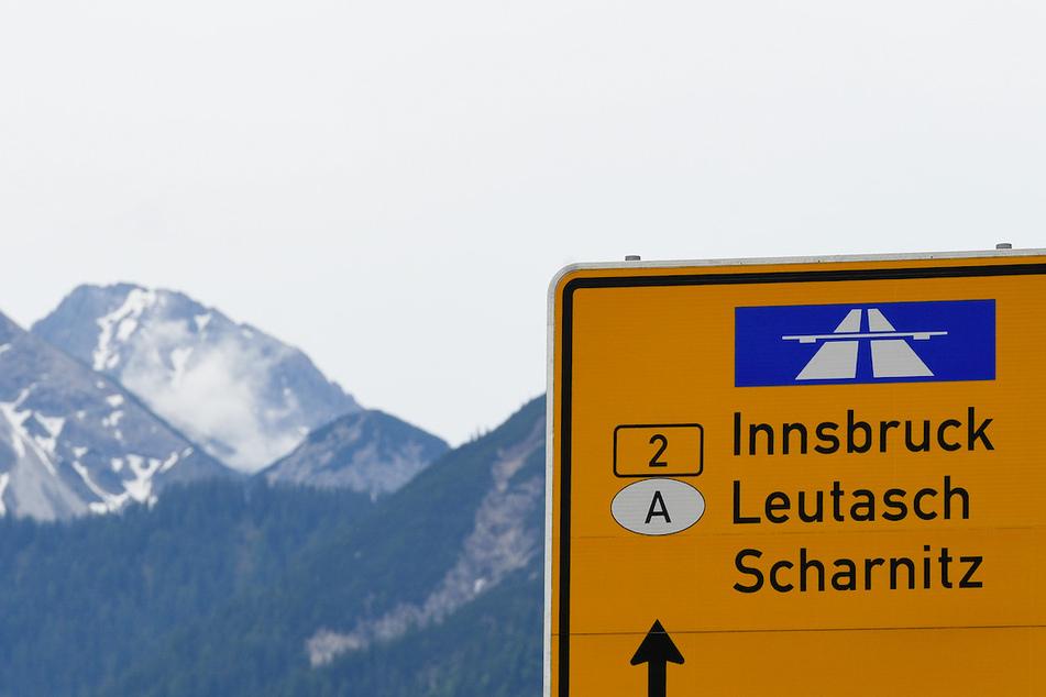 Ein Schild zeigt auf der Landstraße den Weg Richtung Innsbruck in Österreich.