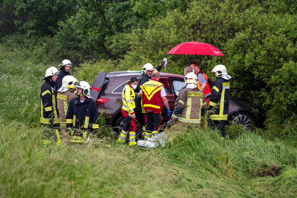 Feuerwehr und Rettungsdienst stehen an dem auf der A4 verunfallten Mercedes und kümmern sich um die schwerverletzten Personen.
