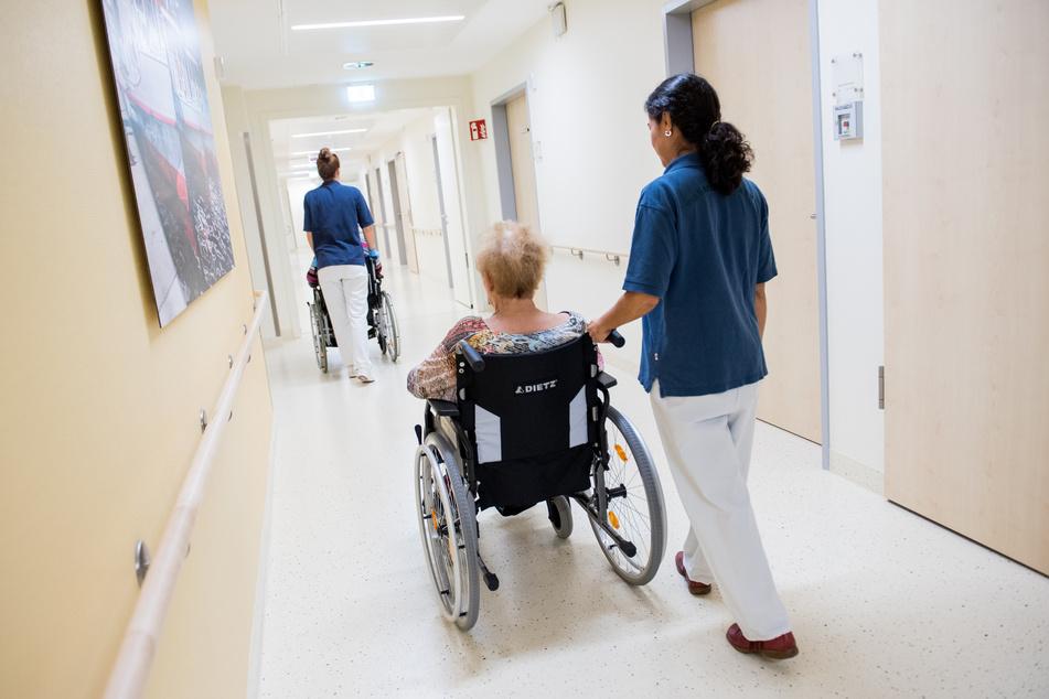 Zwei Pflegerinnen schieben Patienten mit Rollstühlen auf einem Flur in einem Krankenhaus in Schleswig-Holstein.