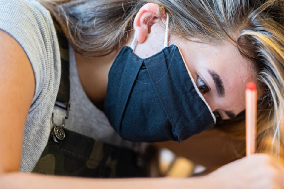 Eine Schülerin mit Maske im Schulunterricht. Die Stadt Köln wagt jetzt einen neuen Versuch bei der Quarantäne für Schüler.