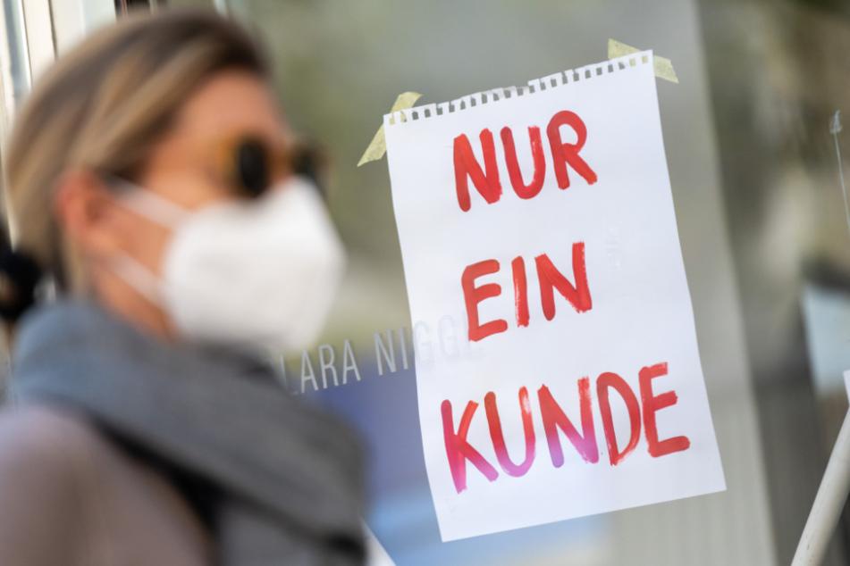 München: Eine Frau mit Nase-Mund-Schutzmaske geht an einem Geschäft vorbei.
