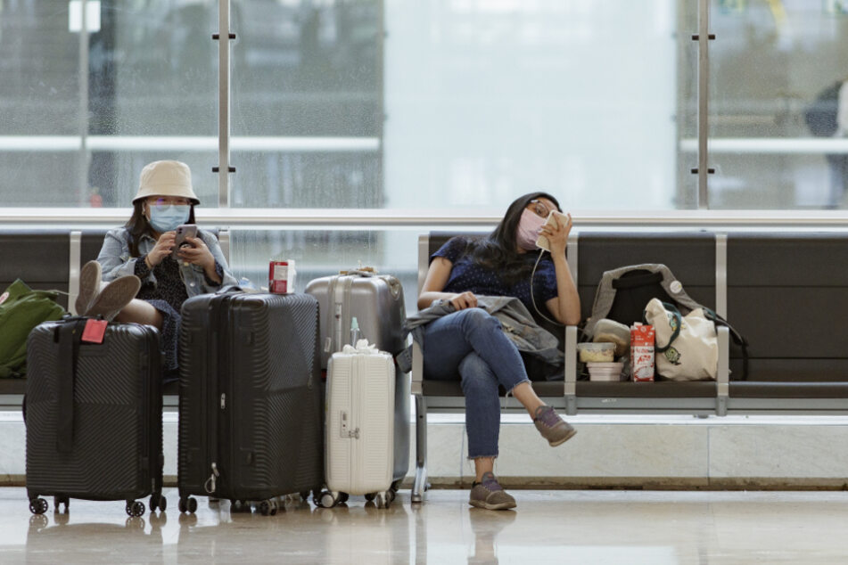 Zwei Passagierinnen sitzen im Terminal 4 des Flughafens Adolfo Suarez Madrid-Barajas.