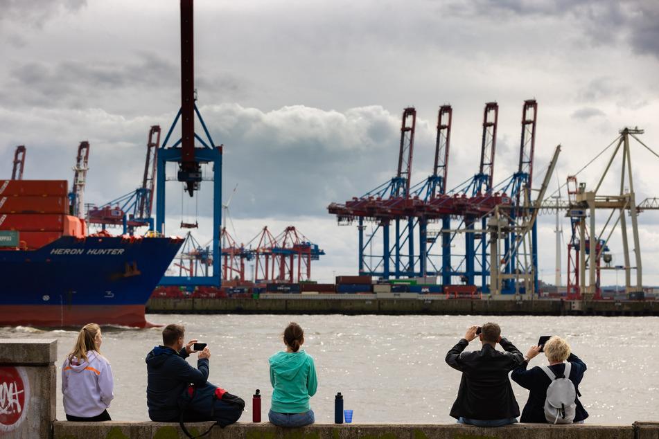 Touristen beobachten bei wolkigem Himmel die Elbe in Hamburg.