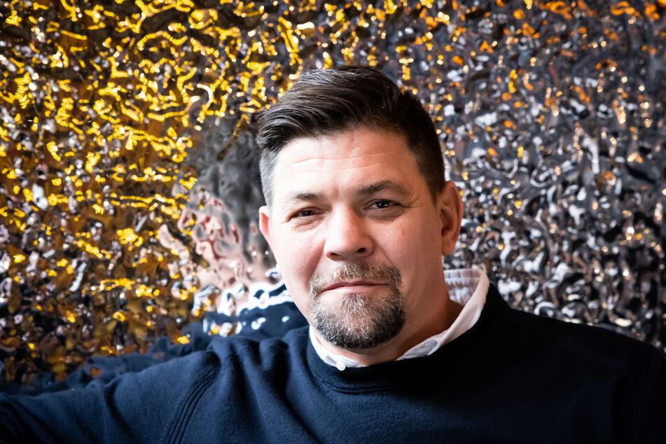 """TV-Koch Tim Mälzer (49) an einem Tisch in den neu gestalteten Räumen der """"Bullerei""""."""
