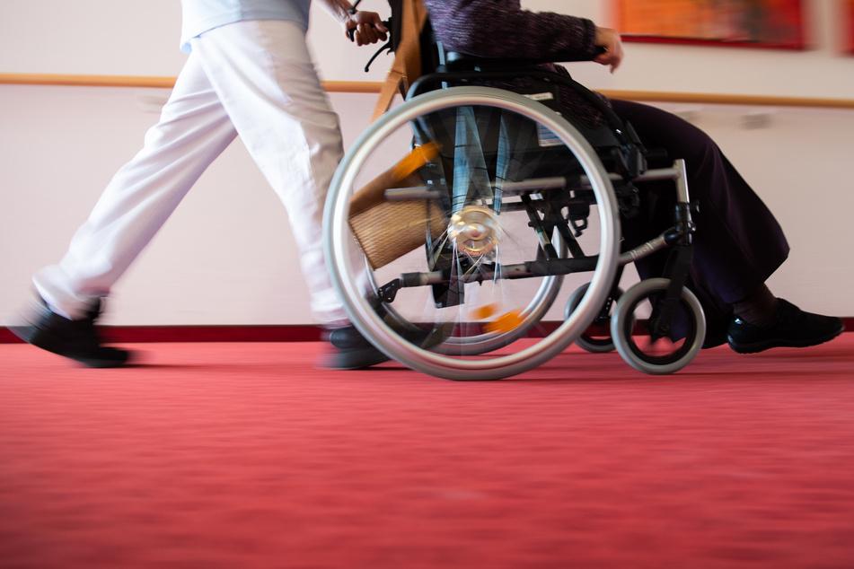 Ein Pfleger schiebt eine Seniorin mit einem Rollstuhl.