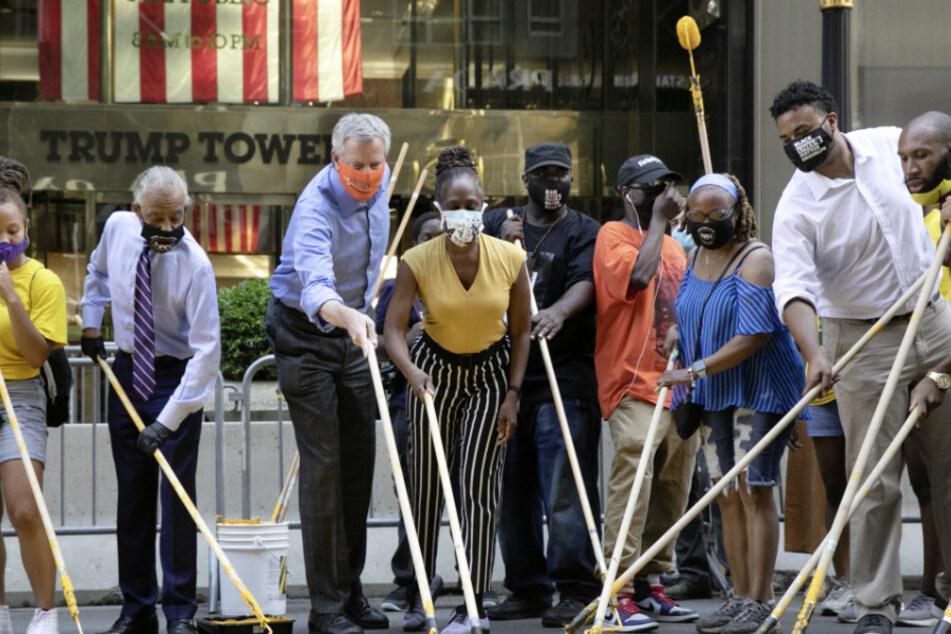 """USA, New York: Bill de Blasio (3.v.l), Bürgermeister von New York, hilft gemeinsam mit seiner Ehefrau Chirlane McCray (4.v.l) und dem US-Amerikanischen Bürgerrechtler Al Sharpton (2.v.l) im Rahmen einer Protestaktion dabei, den Schriftzug """"Black Lives Matter"""" auf die Fifth Avenue vor dem Trump Tower zu malen."""
