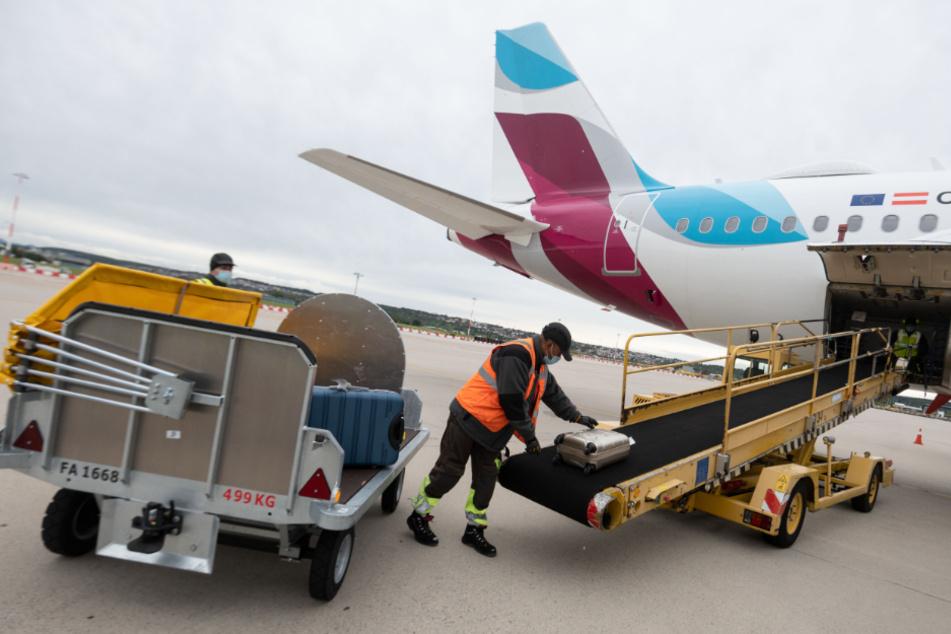 Ein Arbeiter lädt auf dem Vorfeld des Flughafen Stuttgart Gepäckstücke in den Gepäckraum eines Flugzeugs.