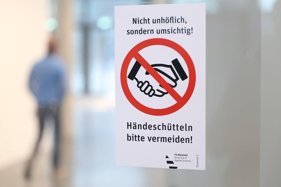 """Blick auf ein Hinweisschild mit der Aufschrift """"Händeschütteln bitte vermeiden!"""" in einem Gebäude der Fachhochschule Bielefeld."""