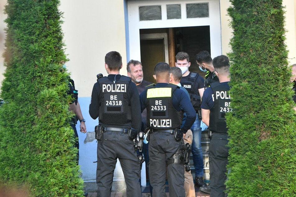 Clan-Chef Issa Remmo steht mit Polizisten vor der Tür der Villa.