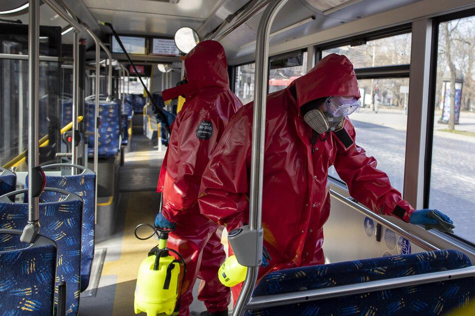 Arbeiter in Schutzanzügen desinfizieren einen öffentlichen Bus in Litauen.