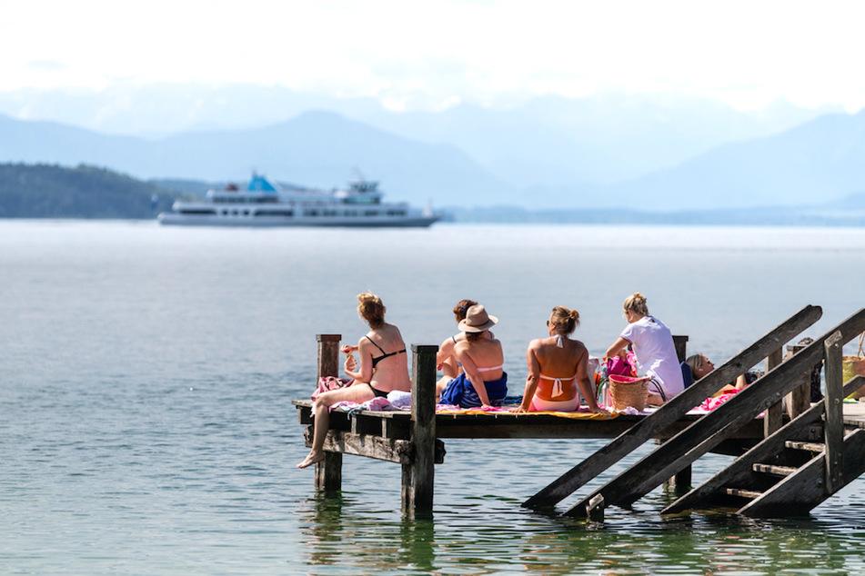Eine Gruppe von Frauen sitzt auf einem Steg am Ufer vom Starnberger See.
