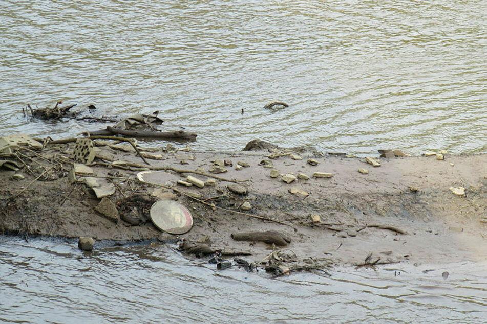 Wird der Wasserstand zur Wartung des Wehrs gesenkt, tauchen überall im Becken Schlamm- und Müllinseln auf.