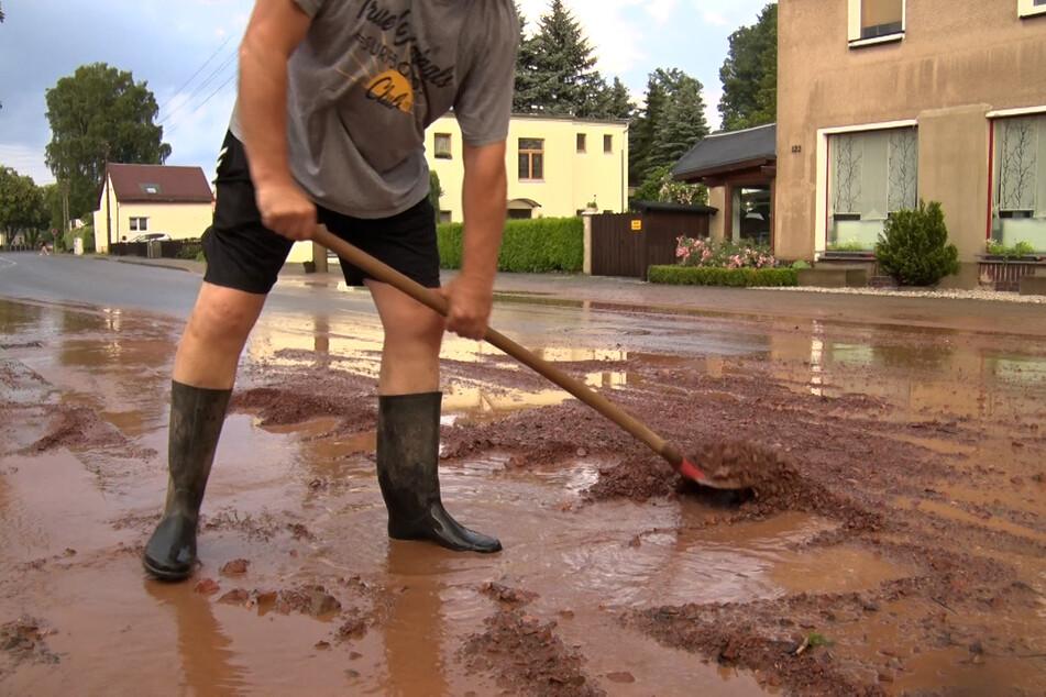 Ein Anwohner befreit eine Straße von Schlamm und Wasser.