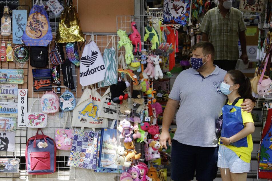 Zwei Personen mit Masken stehen vor einem Geschäft in der Innenstadt von Palma.