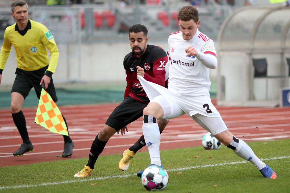 Der Nürnberger Sarpreet Singh (M.) kämpft mit dem Hamburger Moritz Heyer (r.) um den Ball.