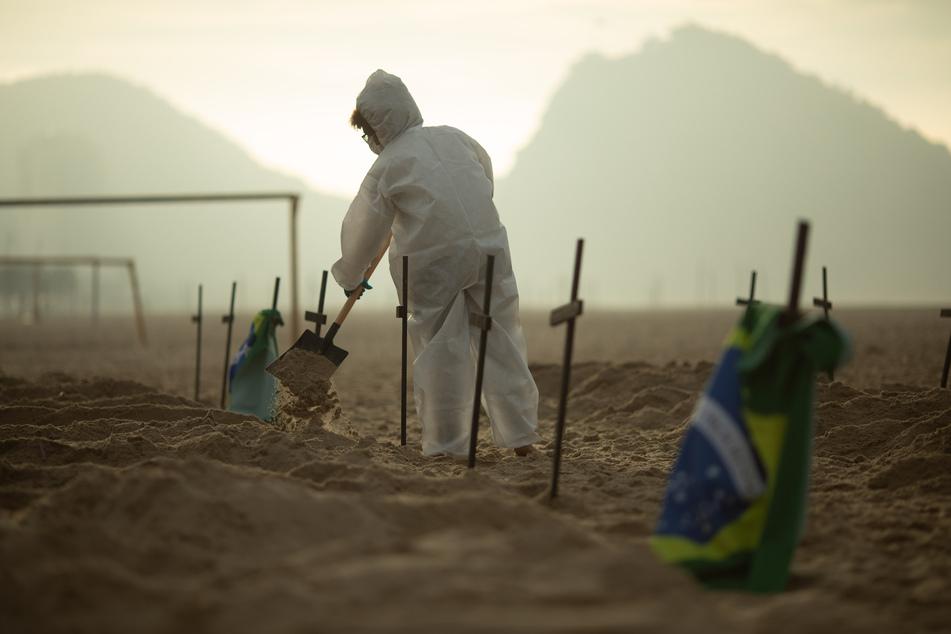 Ein Aktivist der NGO Rio de Paz schaufelt am Strand Copacabana Gräber aus während eines Protests gegen den Umgang der Regierung mit der Corona-Krise. Brasilien ist das von der Coronavirus-Pandemie am stärksten betroffene Land in Lateinamerika.