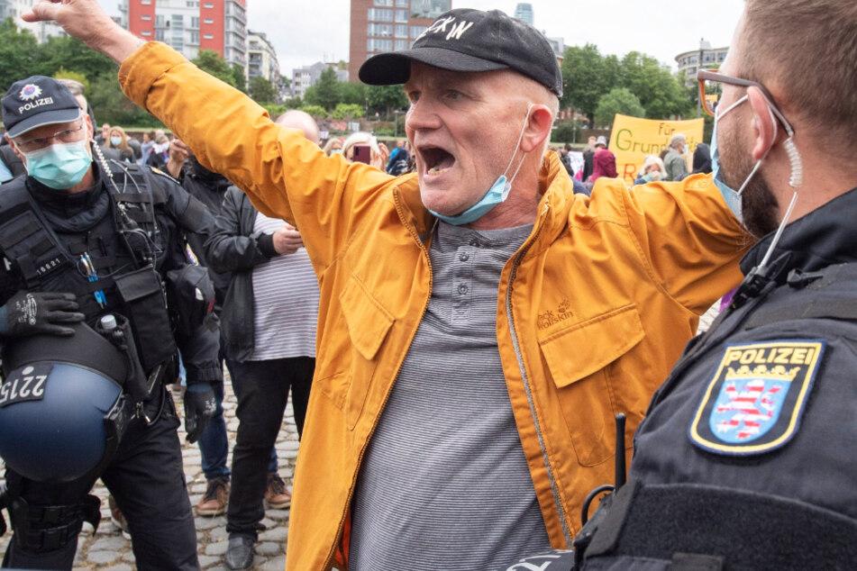 Die Polizei fordert einen Mann in Frankfurt dazu auf, bei einer Demonstration gegen die Corona-Maßnahmen seinen Mundschutz zu tragen.