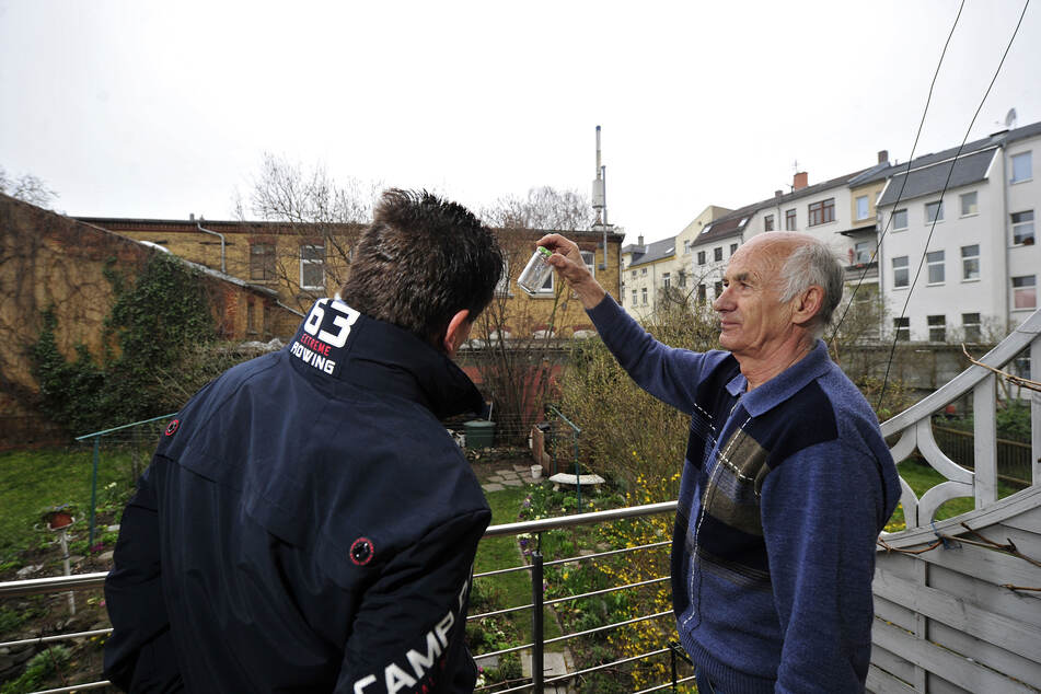 Streit um Blockheizkraftwerk (im Hintergrund): Lothar Zeh (76) zeigt Nachbar Bernhard Bleck (63) ein Glas mit Rußflocken.