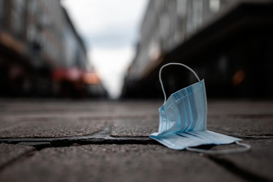 Eine Maske liegt auf dem Boden. Vollständig gegen Corona geimpfte Menschen müssen in den USA einer Empfehlung der Gesundheitsbehörde CDC zufolge in vielen Innenräumen keine Masken mehr tragen.