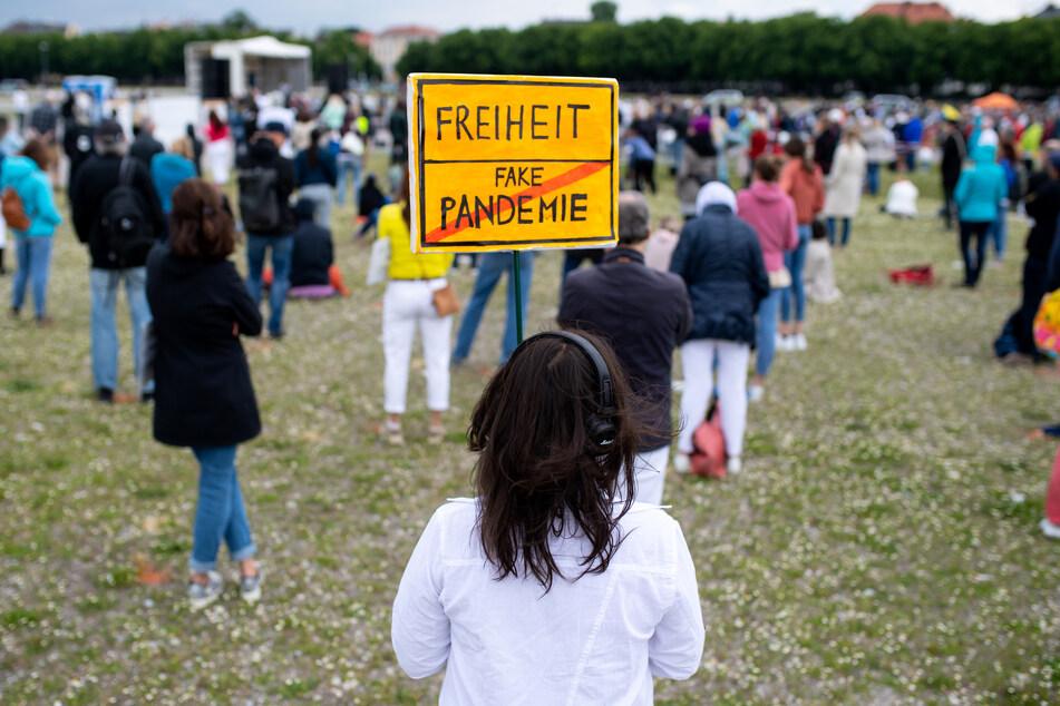 """Eine Teilnehmerin einer Demonstration gegen die Anti-Corona-Maßnahmen der Politik steht auf der Theresienwiese und hält ein Schild mit der Aufschrift """"Freiheit / Fake Pandemie"""" in den Händen."""