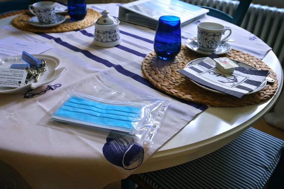 Ein Mundschutz liegt am Frühstückstisch einer Ferienwohnung.