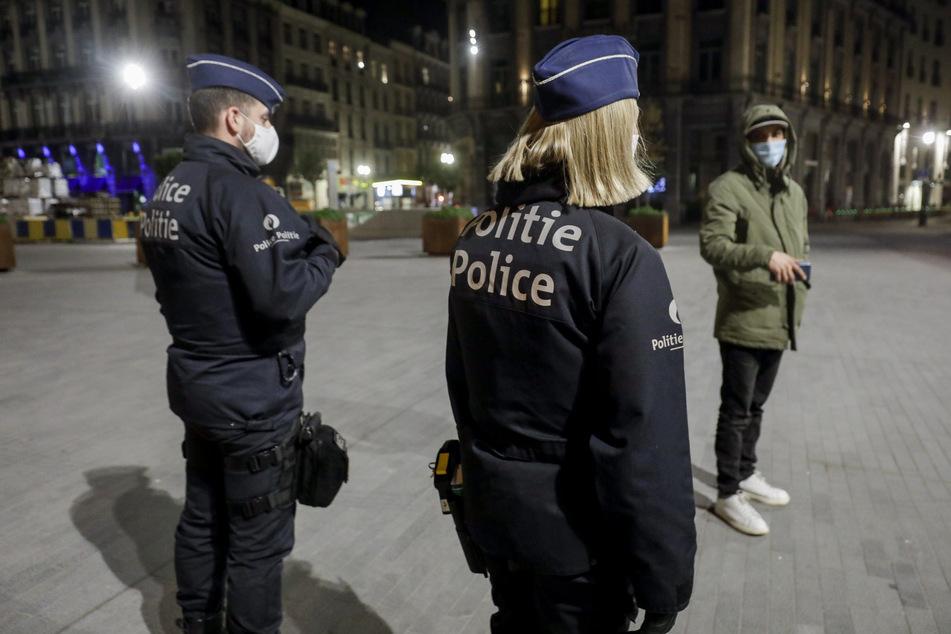 Zwei Polizeibeamte patrouillieren zu Beginn der Ausgangssperre in Brüssel durch die Stadt.