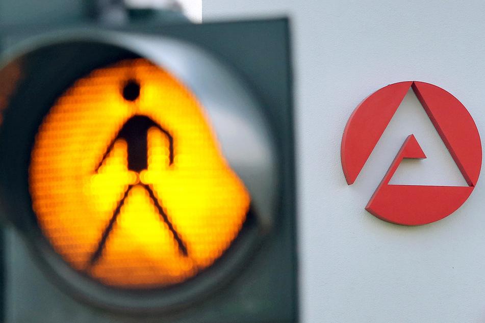 Eine Ampel warnt Autofahrer vor kreuzenden Fußgänger auf dem Weg zur Agentur für Arbeit.