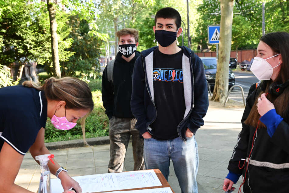 Schülerinnen und Schüler des Heinrich von Gagern-Gymnasiums in Frankfurt werden beim Eintritt in das Schulgebäude registriert.