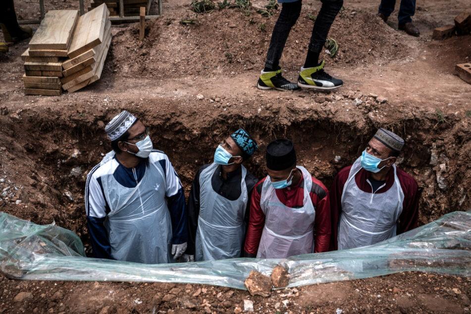 Johannesburg: Bestatter in Schutzkleidung bereiten das Grab für eine am Coronavirus verstorbene Person auf dem Avalon-Friedhof für die Beerdigung vor.