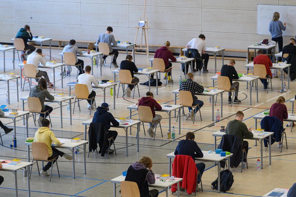 Mit weitem Abstand sitzen Schüler des Dresdner Gymnasiums Bürgerwiese zur Abiturprüfung in Deutsch an ihren Tischen in der Sporthalle.