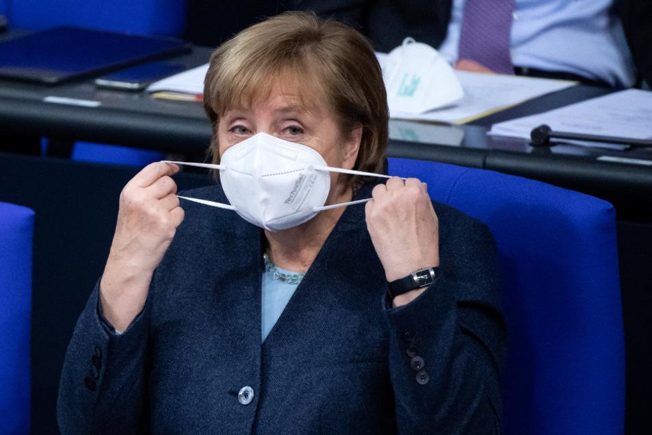 Bundeskanzlerin Angela Merkel setzt sich zu Beginn der Plenarsitzung im Deutschen Bundestag ihre FFP-Maske ab.