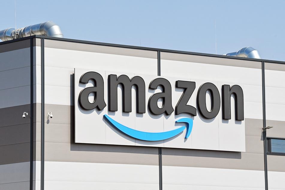 Das Logo von Amazon hängt an einem Versandlager.