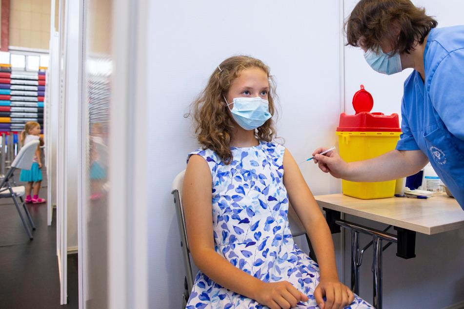 Eine Schülerin wird gegen das Coronavirus geimpft. Die Gewerkschaft Erziehung und Wissenschaft (GEW) wünscht sich mehr Engagement vom Kultus- und Sozialministerium, um die Impfquote bei Schülern nach oben zu treiben. (Symbolbild)